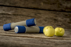Two workout dumbbells and three fresh ripe apples lying on a tex Royalty Free Stock Images
