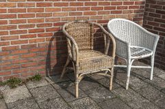 Two worn wicker chairs standing by a surrounded wall stock image
