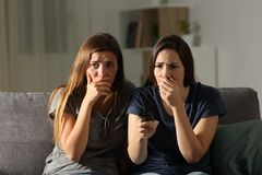 Two worried friends watching tv in the night. Front view portrait of two worried friends watching tv in the night sitting on a couch in the living room at home royalty free stock images