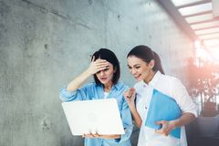 Women rooting for someone online. Two worried girls looking at laptop screen and keeping their fists. They standing indoors Royalty Free Stock Image