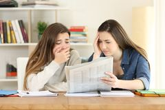Two worried students reading a newspaper. Two worried students reading bad news in a newspaper at home Stock Image