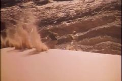 Two wounded men fall down sand dune stock video
