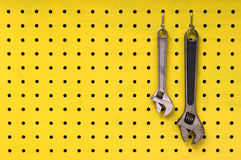 Two wrenches hang from hooks on yellow pegboard. Pair of metal wrenches hang together off of hooks on yellow pegboard Royalty Free Stock Photo
