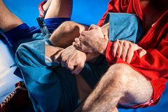 Man wrestler makes submission wrestling. Two wrestlers of grappling and jiu jitsu in a blue and red kimono makes armlock on blue tatami. Close-up Wrestler stock photos