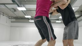 Two wrestlers perform in slow motion. Greco-Roman wrestlers train in the hall in T-shirts and coats. Two wrestlers perform in slow motion. Greco-Roman wrestlers stock footage