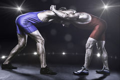 Two wrestlers in stance on stage. Two freestyle wrestlers in red and blue wrestling uniform on stage Stock Photo