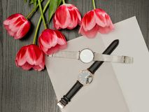 Two wristwatches on a gray sheet and tulips. Fashionable concept, top view.  Stock Images