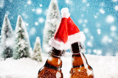 Two xmas beer bottles clink together Royalty Free Stock Image