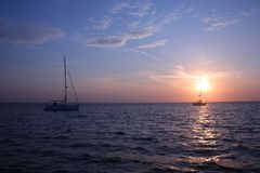 Two yachts at anchor in studland bay with sunrise in the background Royalty Free Stock Photo