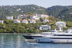 Two Yachts Below Tropical Homes Royalty Free Stock Photos