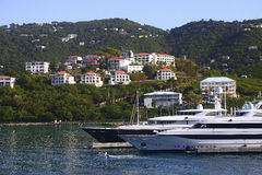 Two Yachts Beneath Tropical Homes Royalty Free Stock Images