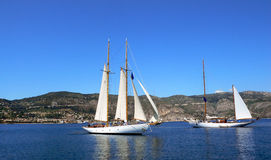 Two yachts meeting. Two classic sailing yachts arriving in a bay Stock Photography