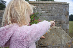 Two yaer old girl pointing out from a castle parapit Stock Photo