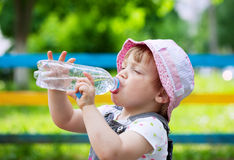 Two-year child drinks from  bottle. Two-year child drinks from plastic bottle in park Stock Photography