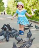 Two-year girl feeding doves Royalty Free Stock Photo