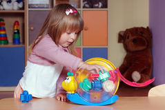 Two-year girl playing and learning in preschool. Child in the nursery builds with blocks Stock Images