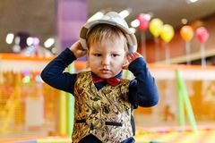 Two-year kid in a hat and tie a butterfly, baby`s birthday. Two-year kid in a hat, waistcoat and tie a butterfly in the children`s room on a blurred background royalty free stock photos