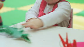Two-year old baby girl plays with toys. Two-year old baby girl  plays with toys at a table at a nursery school. Closeup stock footage