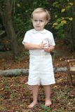 Two year old boy. Dressed in a classic linen summer suit, this cute little boy doesn't seem too happy to have his picture taken Stock Photo