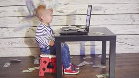 Two year old boy with a computer and falling money. smiling boy sitting at table with laptop and dollar banknotes in air. Concept of successful business stock video