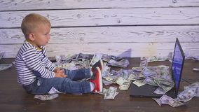 Two year old boy with a computer and falling money. smiling boy sitting at table with laptop and dollar banknotes in air. Concept of successful business stock footage