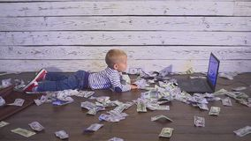 Two year old boy with a computer and money. smiling boy sitting at table with laptop and dollar banknotes. Concept of. Two year old boy with a computer and stock video footage