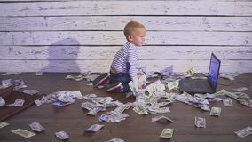 Two year old boy with a computer and money. smiling boy sitting at table with laptop and dollar banknotes. Concept of. Two year old boy with a computer and stock footage