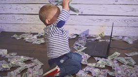 Two year old boy with a computer and money. smiling boy sitting at table with laptop and dollar banknotes. Concept of. Two year old boy with a computer and stock video