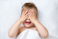 Two year old boy covering his face with hands playing stock photo