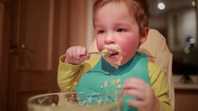 Two year old boy is having dinner independently. Shot on Canon 5D Mark II with Prime L Lenses stock footage