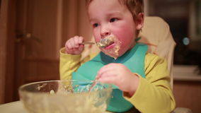 Two year old boy is having dinner and looking into the plate. Royalty Free Stock Images