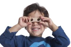 Two year old boy looking through the holes of a block. On white background Stock Image