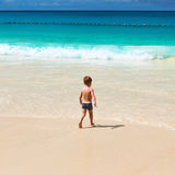 Two year old boy playing on beach Stock Photos