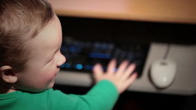 Two year old boy is playing with keyboard. Shot on Canon 5D Mark II with Prime L Lenses stock footage