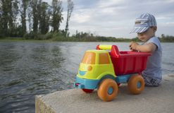 Little boy playing at riverside with dump truck loaded with ston stock photos