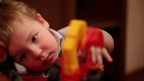 Two year old boy plays with toy trucks. stock video