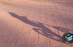 Shadow of a two year old boy riding a blue bike without pedals stock photo