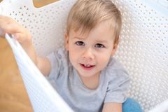 Two year old boy sitting in a box and playing royalty free stock photo