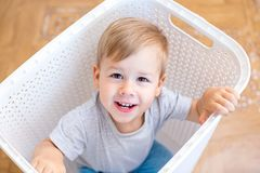 Two year old boy sitting in a laundry basket and playing stock photo