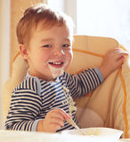 Two year old boy smiles and eating porridge. Royalty Free Stock Image