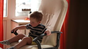 Two year old boy is spinning on chair. Shot on Canon 5D Mark II with Prime L Lenses stock footage