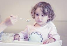 Two-year-old child eats porridge stock images