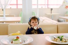 Two year old child sitting at a table in the Cafe royalty free stock image
