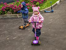 Two year old children riding a scooter in a park.