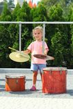 Two year old cute girl learning how to play drums outdoor stock photography