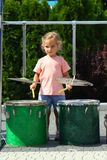 Two year old cute girl learning how to play drums outdoor royalty free stock photos