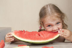 Two-year-old girl eating watermelon with cheerful faces Royalty Free Stock Image