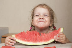 Two-year-old girl eating watermelon with cheerful faces Stock Photos