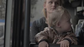 Baby girl on mums lap in the bus. Two year old girl enjoying bus ride sitting on mothers lap stock video footage