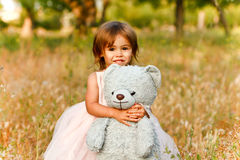 Two-year-old girl in field  carrying stuffed animal. Cute multi-racial, 2 year old girl looks directly at camera while holding her blue stuffed bear.  Little Royalty Free Stock Photo
